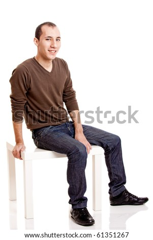 Portrait of a young man seated and smilling, isolated on white - stock photo