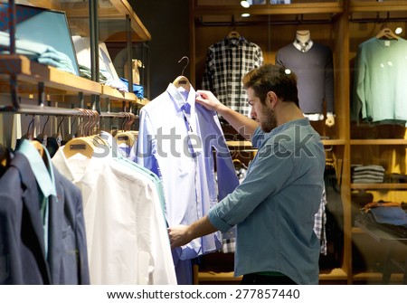 Portrait of a young man shopping for clothes at store - stock photo