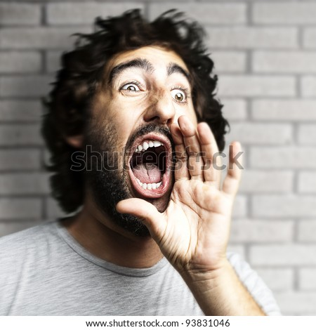 portrait of a young man shouting against a grunge brick wall - stock photo