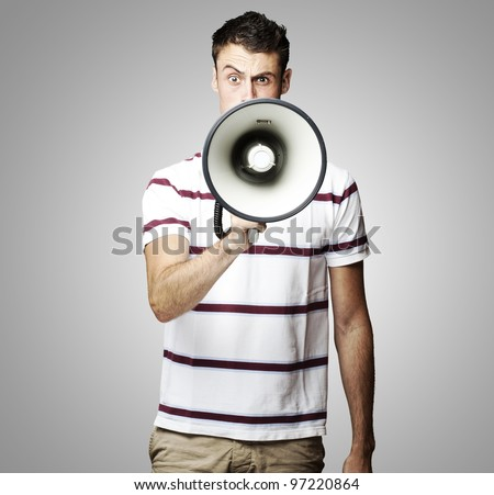 portrait of a young man shouting using a megaphone over a grey background - stock photo