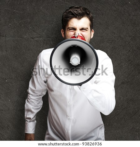 portrait of a young man shouting with a megaphone against a black background - stock photo