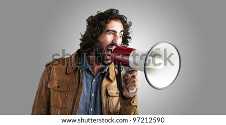 portrait of a young man shouting with a megaphone against a grey background - stock photo