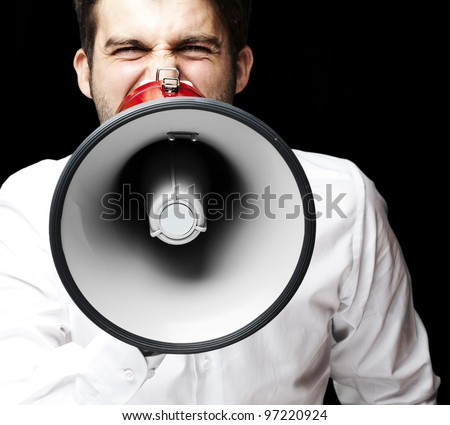 portrait of a young man shouting with a megaphone over a black background - stock photo