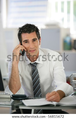 Portrait of a young man sitting at a desk phoning and writing on a document