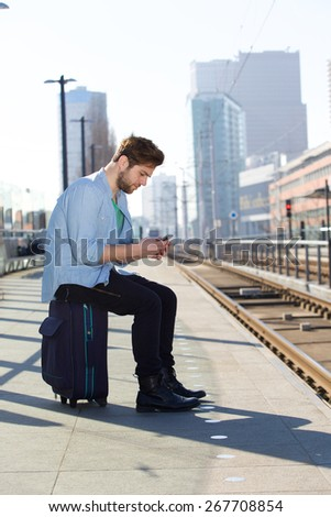Portrait of a young man sitting at train station platform text messaging  - stock photo