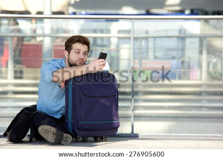 Portrait of a young man sitting on floor looking at mobile phone at airport  - stock photo