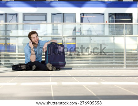 Portrait of a young man sitting on floor with bag and talking on mobile phone - stock photo