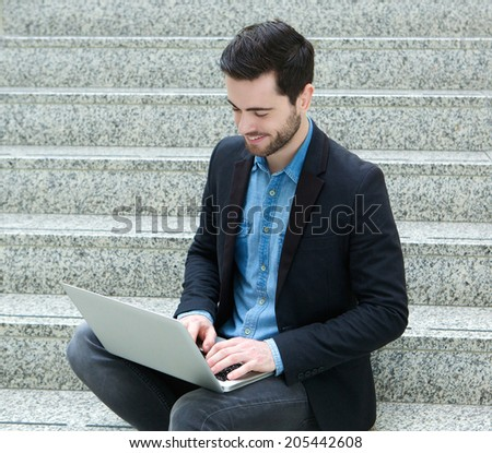 Portrait of a young man sitting on steps smiling with laptop - stock photo