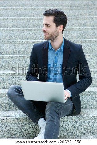 Portrait of a young man sitting on steps with laptop - stock photo