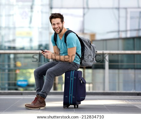 Portrait of a young man sitting on suitcase and sending text message  - stock photo