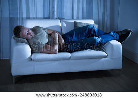 Portrait Of A Young Man Sleeping On Couch - stock photo