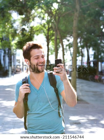 Portrait of a young man smiling and holding mobile phone - stock photo