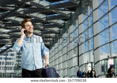 Portrait of a young man smiling at station with bag and mobile phone - stock photo