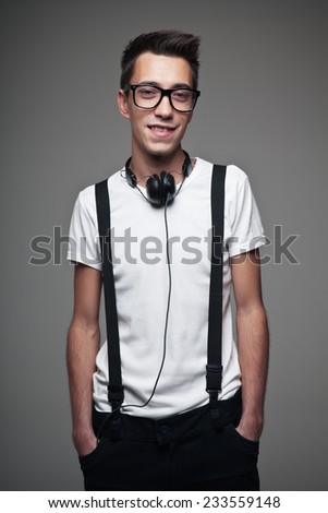 Portrait of a young man smiling with headphones over a gray background - stock photo