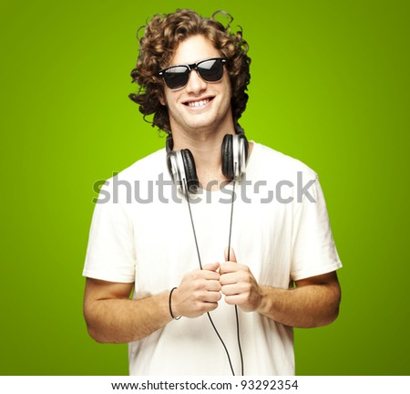 portrait of a young man smiling with headphones over a green background - stock photo