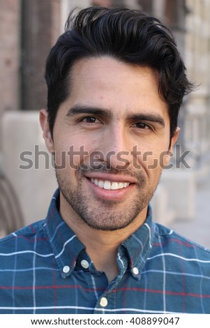 Portrait of a young man smiling with urban background