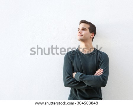 Portrait of a young man standing against white background with arms folded - stock photo
