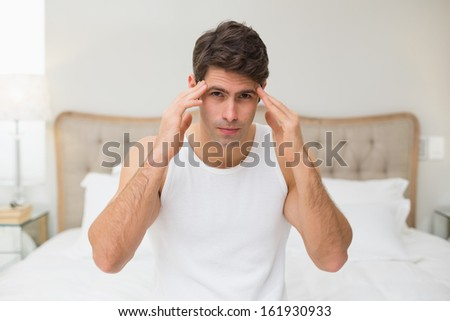 Portrait of a young man suffering from headache in bed at home