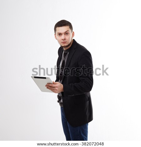 Portrait of a young man surprised with the tablet