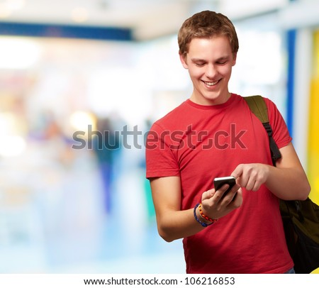 portrait of a young man touching a mobile screen indoor