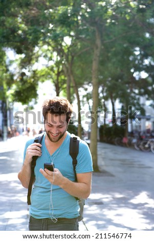 Portrait of a young man traveling with backpack and mobile phone - stock photo