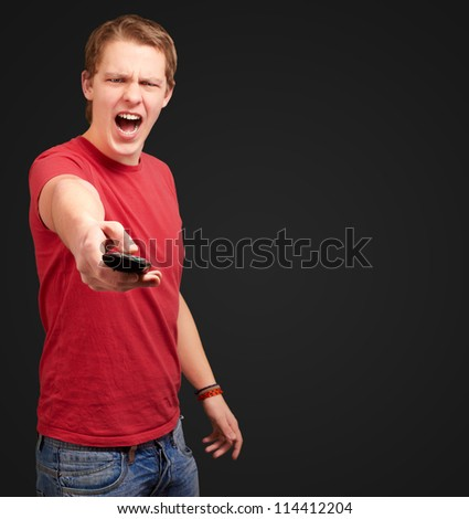 portrait of a young man using remote control on black background - stock photo