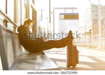 Portrait of a young man waiting at train station platform with mobile phone - stock photo