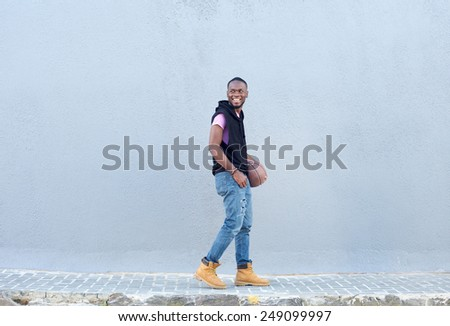 Portrait of a young man walking on sidewalk with basketball