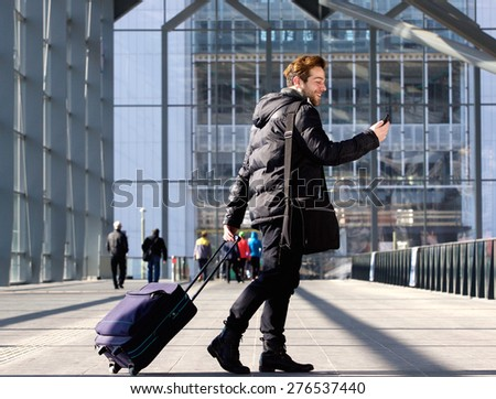 Portrait of a young man walking with suitcase and looking at mobile phone - stock photo