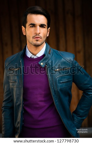 portrait of a young man wearing blue leather jacket against grunge wooden door - stock photo