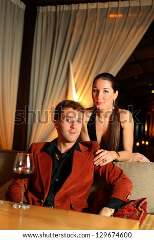 portrait of a young man who sits and beautiful girl standing next - stock photo