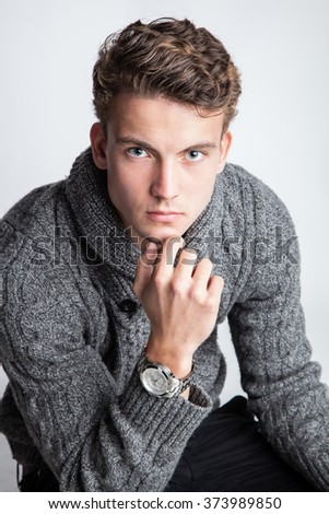 Portrait of a young man with a grey pullover - stock photo
