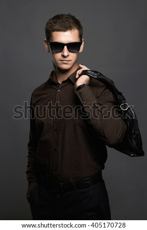 Portrait of a young man with a handbag. Handsome boy in sunglasses