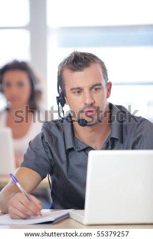Portrait of a young man with a headset in front of a laptop computer - stock photo