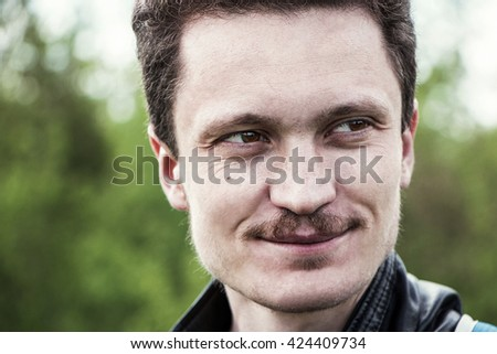 portrait of a young man with a mustache outdoors in spring