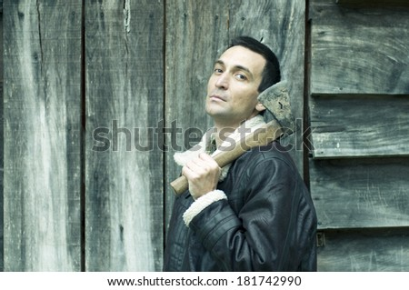 portrait of a young man with an ax in front of the old wooden planks - stock photo