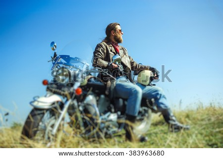 Portrait of a young man with beard sitting on his cruiser motorcycle and relaxing after driving. Man is wearing leather jacket and blue jeans. Low point of view. Tilt shift lens blur effect - stock photo
