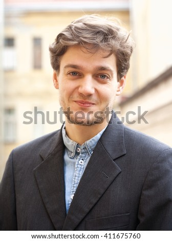 Portrait of a Young Man with Brown Hair Outdoors. - stock photo