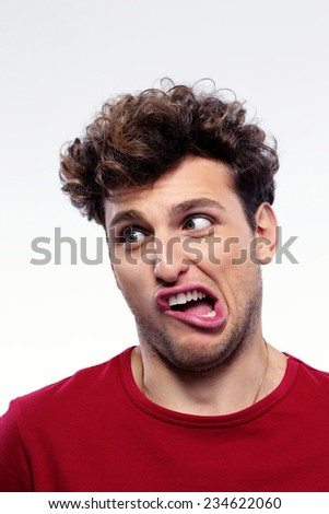 Portrait of a young man with funny expression on his face - stock photo