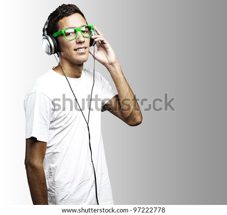 portrait of a young man with green glasses listening to music on a grey background - stock photo