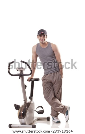 Portrait of a young man with hand in pocket standing next to an exercise bike over white background - stock photo