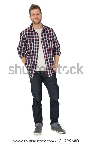 Portrait of a young man with hands in pockets over white background
