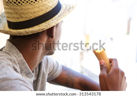 Portrait of a young man with hat eating ice cream and looking away - stock photo