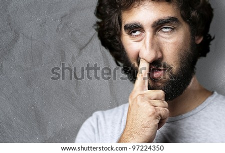 portrait of a young man with his finger in his nose against a grunge background - stock photo