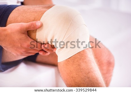 Portrait of a young man with injured leg at home - stock photo