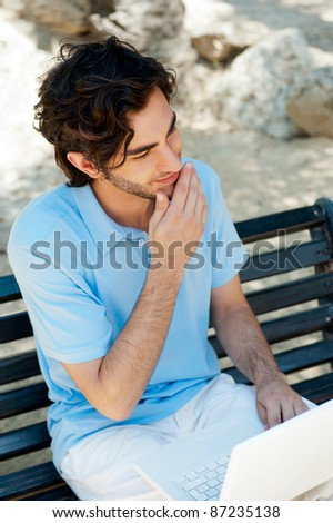 Portrait of a young man with laptop outdoor sitting on bench