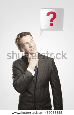 Portrait of a young man with red question mark above his head.Conceptual image of a open minded man. On a gray background - stock photo