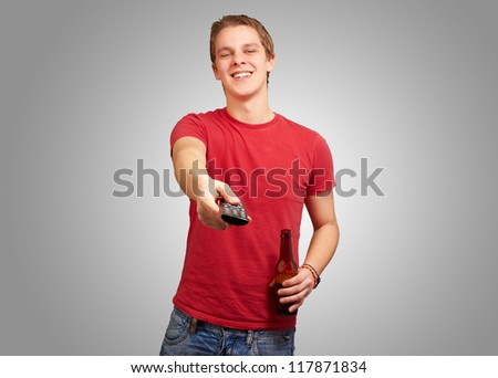 portrait of a young man with remote control on gray background - stock photo