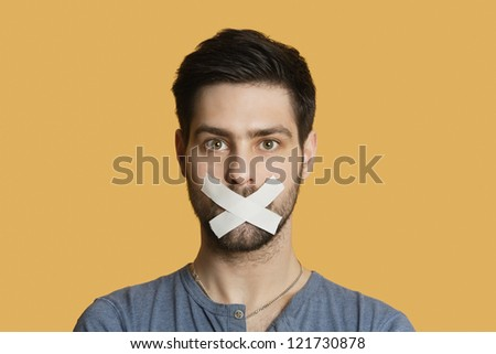 Portrait of a young man with tape on mouth over colored background - stock photo