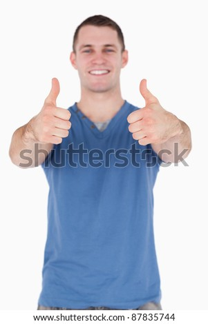 Portrait of a young man with the thumbs up against a white background